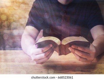 a young man reading holy bible on wooden table, double exposure with image of wooden cross on his t-shirt, christian concept show Jesus is the center