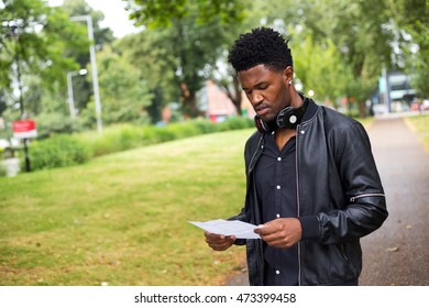 young man reading a letter outdoors