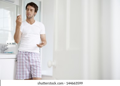 Young man reading pill bottle in bathroom