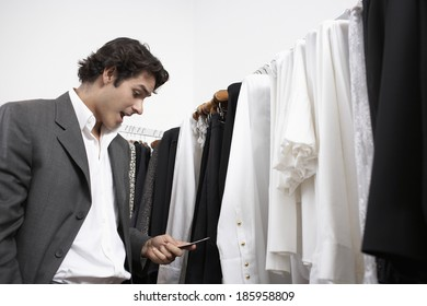 Young man reading price tag in clothing store
