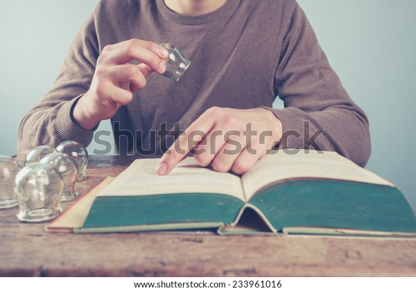 A young man is reading and studying cupping therapy