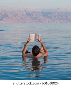 Young man reads a book floating in the waters of the Dead Sea in Israel