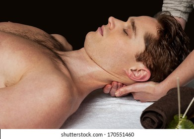 Young man receiving head massage at health spa