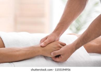Young man receiving massage in salon, closeup