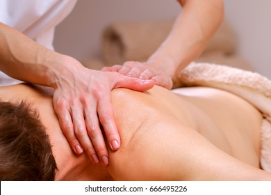 Young man receiving shoulder and back massage from therapist in spa