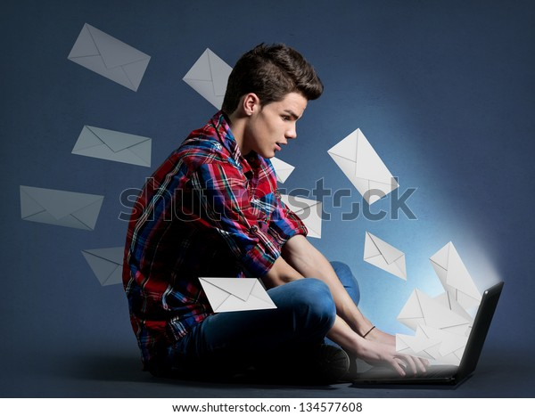 Young man receiving tons of messages on laptop, communication concept
