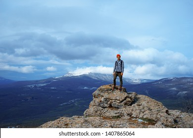 Young man in red hat on the top of the mountain
