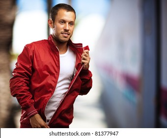 young man with red jacket against a city street background