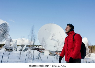 Young man in red jacket with backpack standing near the radio observatory with big satellite dishes or radio antennas in the forest in winter. Norway