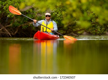 young man in red kayak in tropical destination