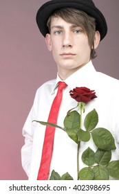 Young man with red rose flower. Love and reflection.