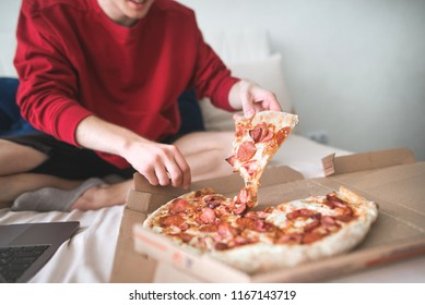 Young man in a red sweatshirt sits at home on a bed and takes an appetizing piece of pizza from the box. Men's hands take a delicious piece of pizza. The teenager is going to eat a piece of pizza