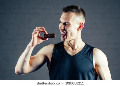 a young man refuses chocolate and sugar in the gym