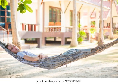 Young man relax in hammock under palm trees on tropical beach