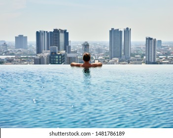 Young man relax on the edge of the roof top swimming pool. Summer vacation concept