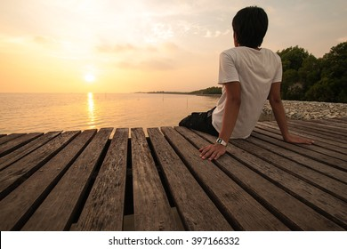 Young man relax siting on pier of sea beach looks forward with sunset sky in Summer background with copyspace for label text banner.