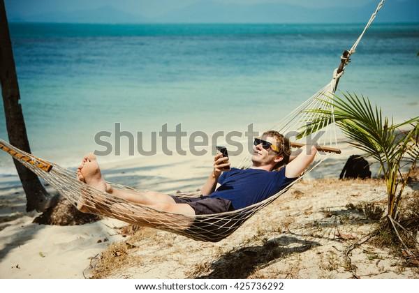 Ein junger Mann entspannt sich in einer Hängematte am Strand, während er auf seinem Smartphone Nachrichten checkt. Tonbild