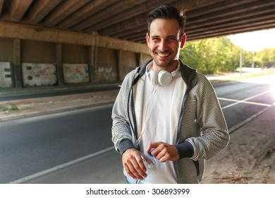 Young man relaxing after jogging.Looking at camera and smiling.