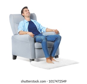 Young man relaxing in cozy armchair on white background