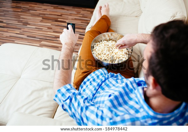 Young man relaxing in front of TV