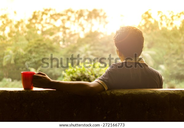 Young man relaxing in a garden having hot coffee in afternoon