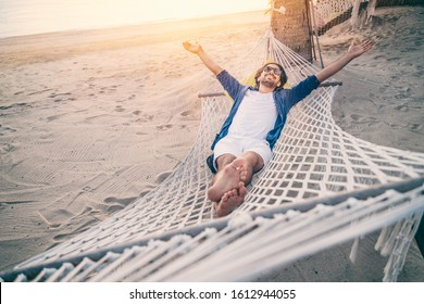 Young man relaxing in hammock on beach. Happiness, freedom of vacation and travel concept. Open arms.