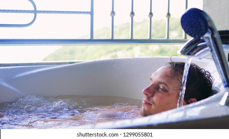 Young man relaxing in the Jacuzzi on tropical island.