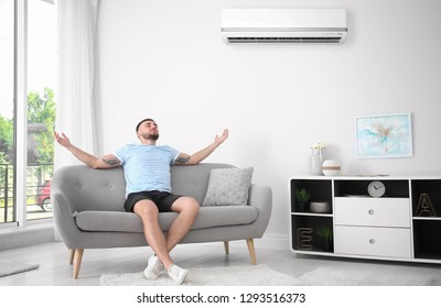 Young man relaxing near air conditioner at home