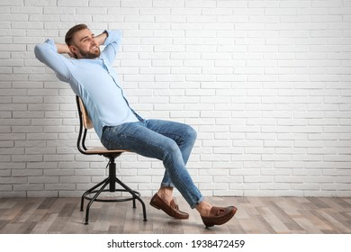 Young man relaxing in office chair near white brick wall indoors, space for text