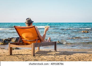 Young Man Relaxing on Chair Near the Sea and Drinking Cocktail Mojito
