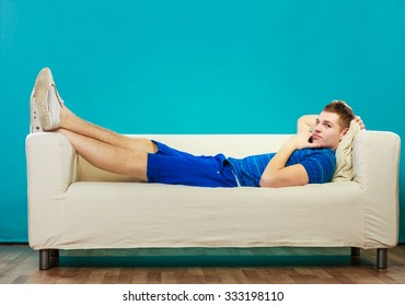 Young man relaxing on couch, teen pensive boy laying lazy on bed blue background