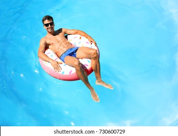Young man relaxing on inflatable donut in swimming pool