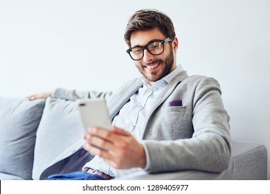 Young man relaxing on sofa and using smartphone