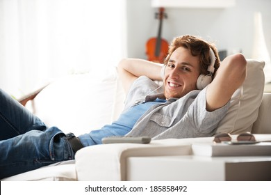 Young man relaxing on sofa with headphones in the living room.