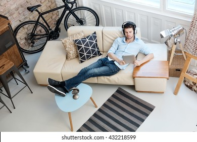 Young man relaxing on sofa, using tablet computer, listening to music at home.
