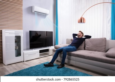 Young Man Relaxing On Sofa Near Television At Home