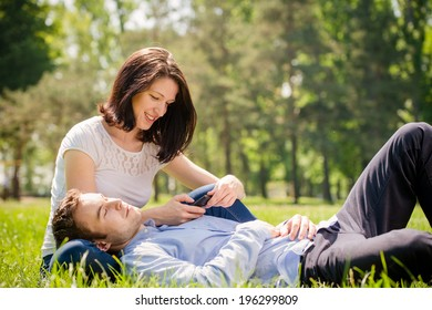 Young man is relaxing on woman's knees while she is playing with smartphone
