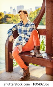 Young Man Relaxing Outside. Dressing in a long sleeve shirt, red pants, brown boots, a young guy is causally sitting on the bench by a lake. City buildings in background. Instagram Hefe filter effect.