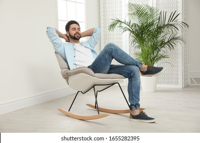 Young man relaxing in rocking chair at home