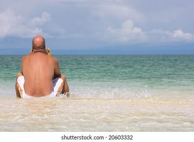 young man relaxing, sitting on sandbank in clear blue water