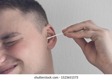 Young man reluctantly cleans his ears with a cotton swab