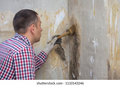 young man removing of mold and fungus from room wall with brush and antiseptic