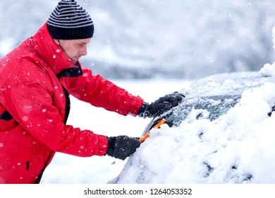 young man removing snow from car. Man cleaning snow from car windshield with brush, close up. Snowy winter weather. Car in snow after snowstorm. Transportation, winter, weather and vehicle concept