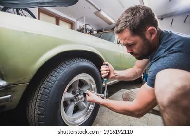 Junge Leute, die Räder oder Reifen aus einem alten Vintage-Auto aus den 60er oder 70er Jahren in seiner Heimgarage entfernen. Werkzeuge sind um die Ecke zu sehen.