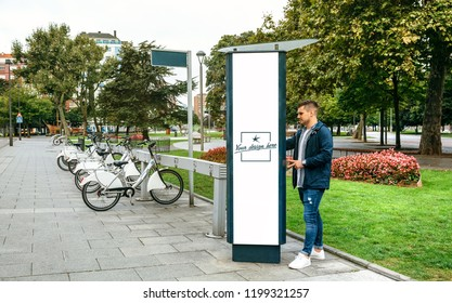 Young man renting a bicycle in a post with customizable poster outdoors