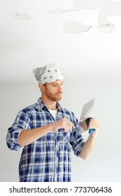 Young man repairing ceiling with plaster