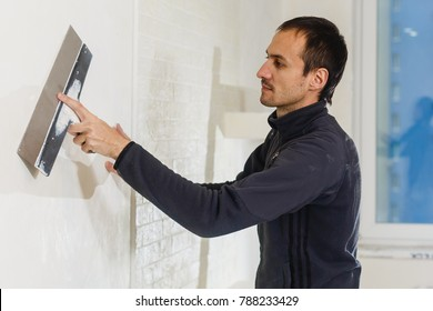 Young man repairing hole in a wall