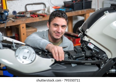 a young man repairing the motorcycle