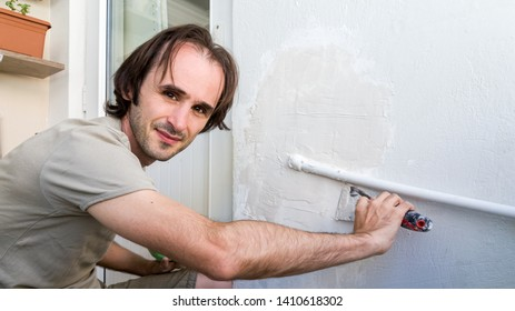 Young man repairing wall at his apartment, applying plaster mix on the wall. Easy home renovating concept.