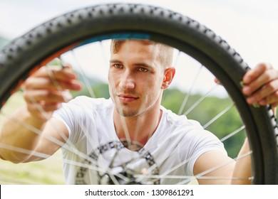 Young man repairs tire hoop of mountainbike after breakdown